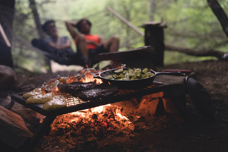 A woman and man sit by a camp fire with delicious food