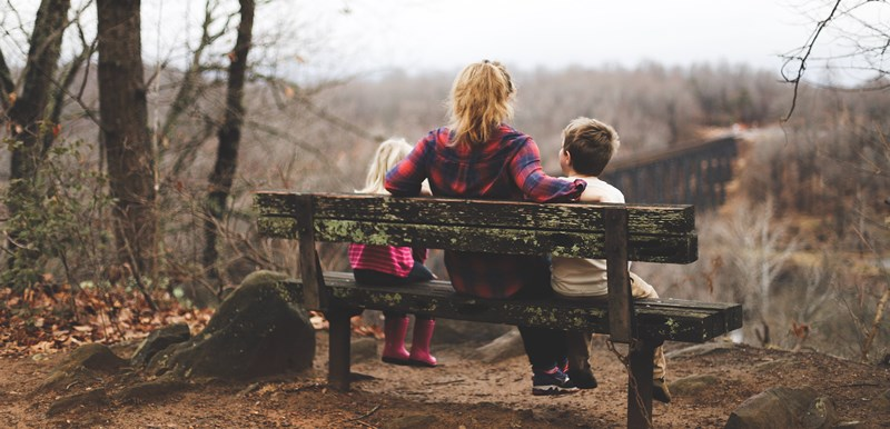Woman and two children sit admiring outdoor viewpoint